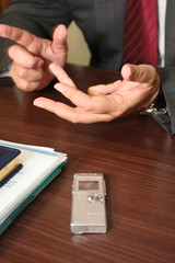 Hands of businessman giving an interview being recorded