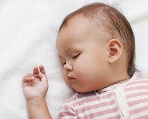 little girl sleeping on a white towel
