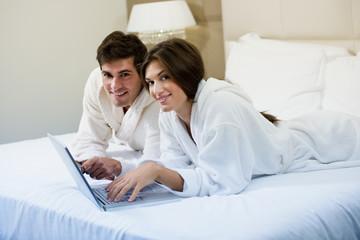 Couple Working iI Bed