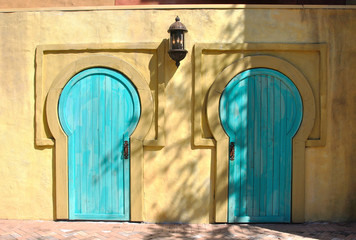 A pair of african style doors on a yellow house