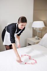Maid Preparing Bed For Honeymooners