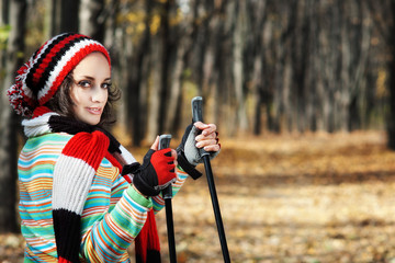 young woman and Nordic walking poles in autumn forest alley