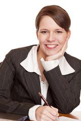 Attraktive Geschäftsfrau sitzt im Büro und arbeitet motiviert