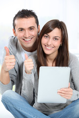 Young couple sitting on sofa with electronic pad