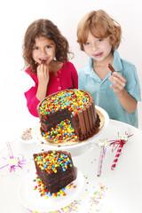 A couple of kids enjoy a chocolate cake