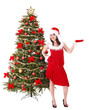 Girl in santa hat by christmas tree. Isolated.