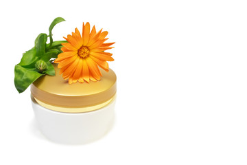 Jar of moisturizing cosmetics with calendula flower