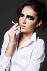 Beautiful woman model smoking a cigarette. Rock make-up