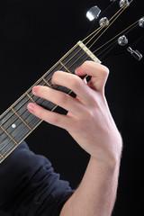 Human hand taking  C-major accord at guitar