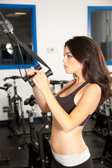 Young beautiful brunette working out in a gym
