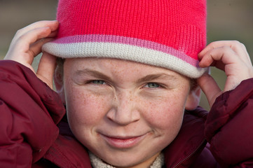 Young girl with freckles putting on knit cap