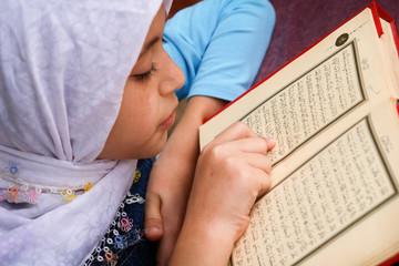 Little girl reads the holy Koran