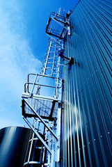 Industrial zone, Steel tanks and stairs against blue sky