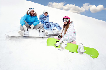 Three young girls sit on snow