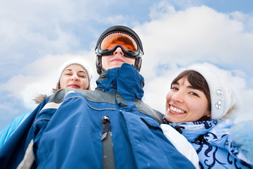 Smiling girls in blue and man in sky mask