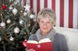 moderne seniorin liest vor dem weihnachtsbaum