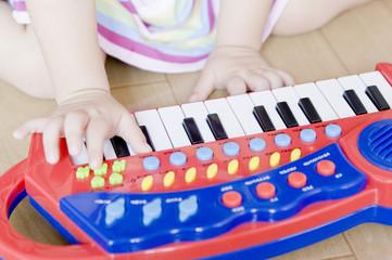 おもちゃのピアノを弾く女児