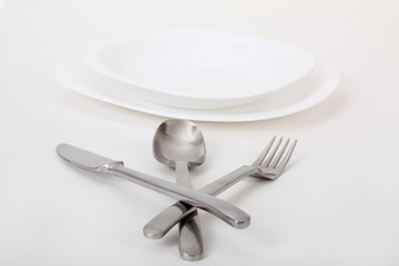 fork and knife and spoon and white plates