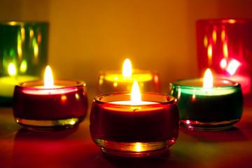Горящие свечи в разноцветных стеклянных подсвечниках