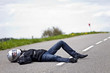 motard accidenté allongé sur route après accident de moto