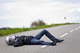 motard accidenté allongé sur route après accident de moto