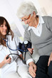 Closeup of nurse checking senior woman blood pressure