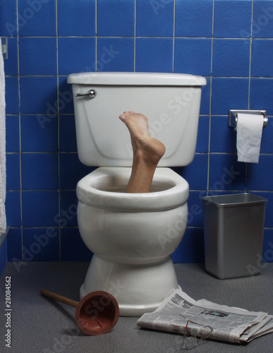 Foot reaches up through the seat from out of a toilet.