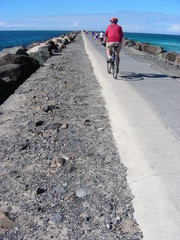 Man Wearing a Red Top Cycling On a Jetty