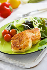 Two potato cakes on a plate with fresh green salad