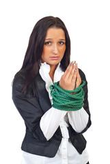 Tied businesswoman praying