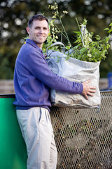 A mid-adult man recycling garden waste