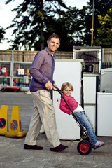 A father pushing his daughter on a trolley in a recycle center