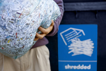 A man recycling a bag of shredded paper