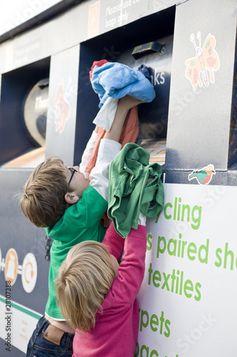 Two young children recycling clothes