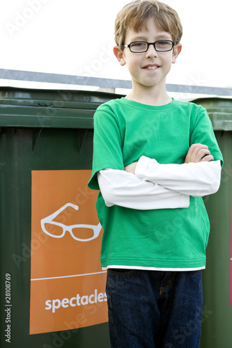 A young boy standing in front of a recycling bin for spectacles