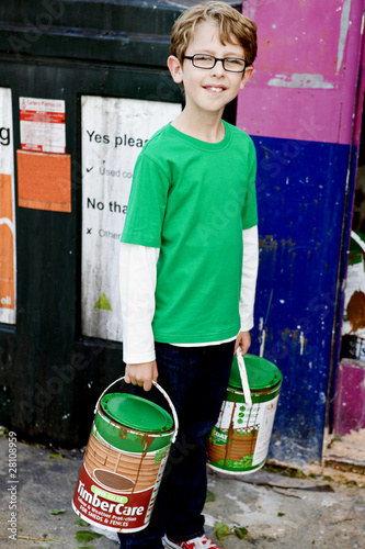 A young boy recycling tins of paint