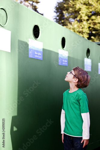 A young boy looking at a recycling container for glass bottles