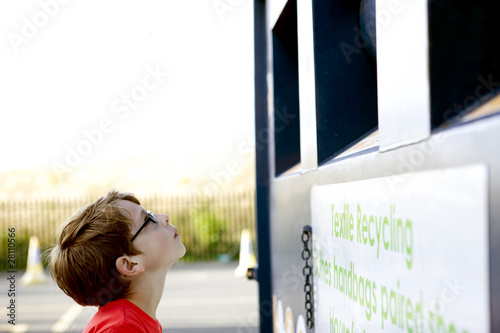 A young boy looking at a recycling container for textiles