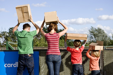 A family disposing of cardboard boxes at a recycling centre