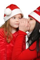 Girl whispers in child ear