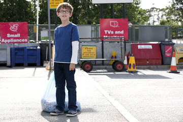 A young boy standing in a recycling centre