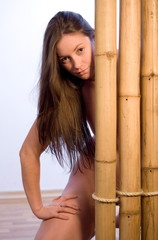 Young sexy brunette hides behind a bamboo fence.