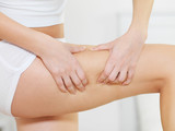 Female squeezes cellulite skin on her legs poster