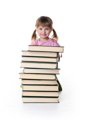 Cute little girl sit near a stack of big books