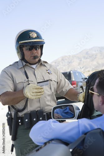 Highway patrol officer examines man's driving license