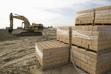 Digger and stacked bricks on construction site