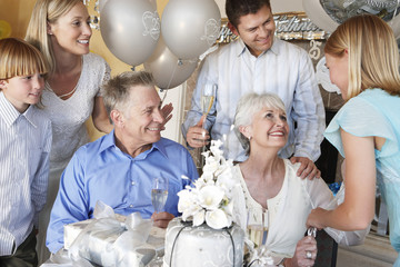 Grandmother smiling at granddaughter at party with whole family