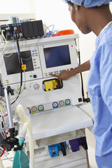 Female surgeon operating medical equipment