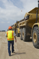 Worker walking near trucks at landfill site
