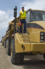 Worker standing on truck at landfill site, portrait